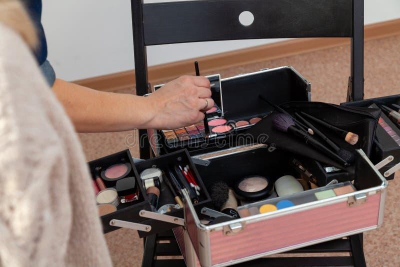 Ein Satz Berufskosmetik im offenen Abschluss des Kastens oben mit Inhalt Maskenbildnermädchen bei der Arbeit, im Studio des Antli stockfoto