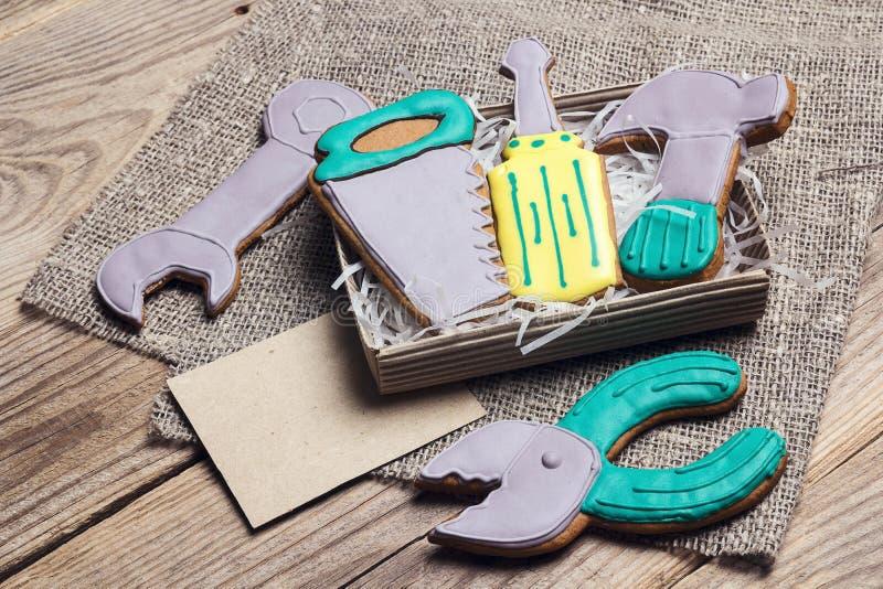 Ein Satz des Lebkuchens in Form von Handwerkzeugen auf einem Holztisch mit leerer Karte für Text Geschmackvolle kreative Plätzche lizenzfreies stockbild