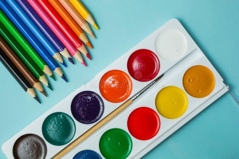 Ein Satz f?r Kreativit?t und Zeichnung: Aquarelle und mehrfarbige Bleistifte auf einem blauen Hintergrund Beschneidungspfad einge stockfotografie