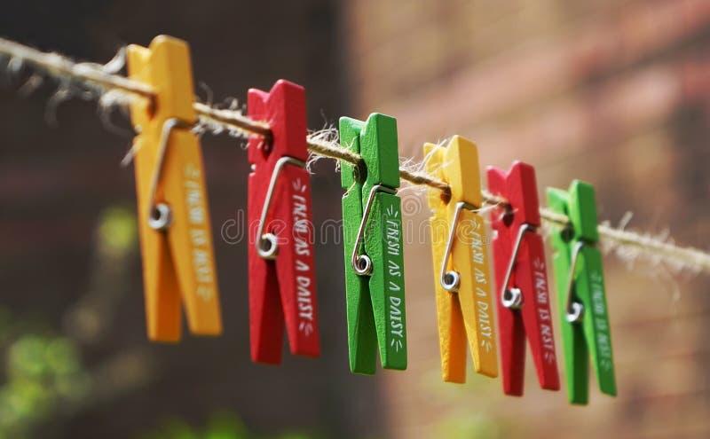 Ein Satz farbige Grün-, Roten und Gelbenhölzerne Klammern auf einer Weinleseschnur lizenzfreie stockfotografie