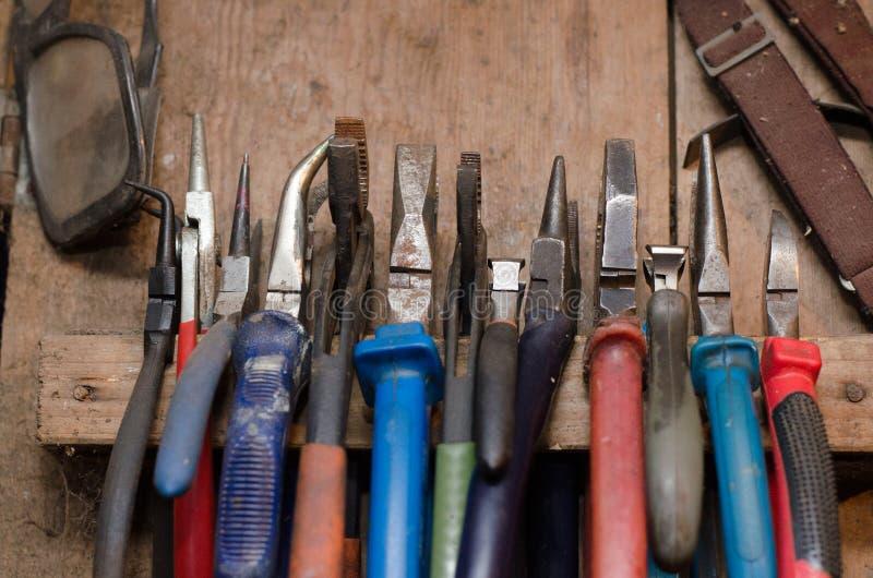 ein Satz farbige Zangen, die am Arbeitsplatz in der Werkstatt hängen lizenzfreies stockfoto