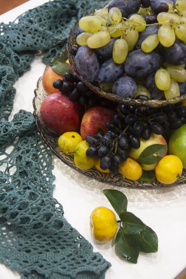 Ein Satz Früchte in den schwarzen und gelben Trauben eines Kojenvase -, Pflaumen, Tangerinen, Äpfel lizenzfreie stockbilder