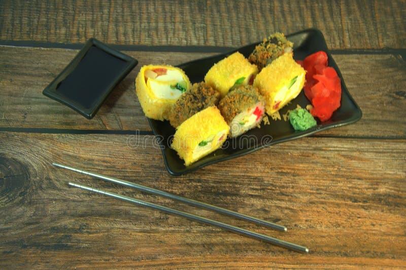 Ein Satz gebratene Sushi mit Ingwer und Wasabi auf einer keramischen Platte mit Sojasoße und Essstäbchen auf einem Holztisch Naha lizenzfreie stockfotos