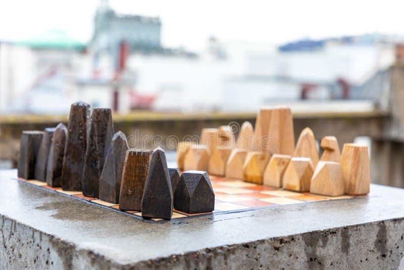 Ein Satz handgemachtes hölzernes Schach des Steins auf Steintabelle im Haus im Freien vor den Spielanfängen stockbilder
