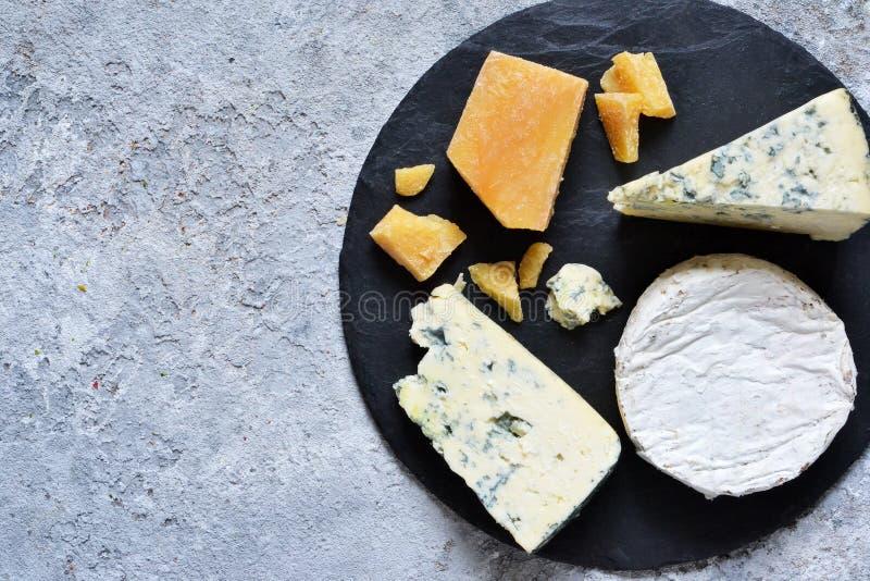 Ein Satz Käse: Briekäse, Blauschimmelkäse, Parmesankäse, Camembert auf einem Schieferbrett Platte mit Zartheit Ansicht von ob stockfotos