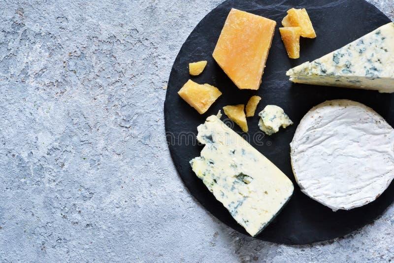 Ein Satz Käse: Briekäse, Blauschimmelkäse, Parmesankäse, Camembert auf einem Schieferbrett Platte mit Zartheit Ansicht von ob lizenzfreie stockbilder