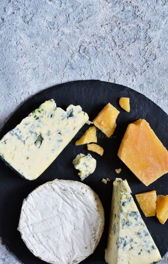 Ein Satz Käse: Briekäse, Blauschimmelkäse, Parmesankäse, Camembert auf einem Schieferbrett Platte mit Zartheit Ansicht von ob stockbilder