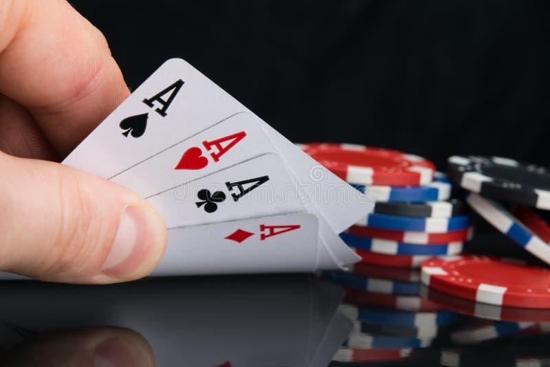 Ein Satz Karten der Spitze vier, in der Hand für das Betrachten, auf einer schwarzen Tabelle mit Reflexion, mit einer zerstreuten stockfotos
