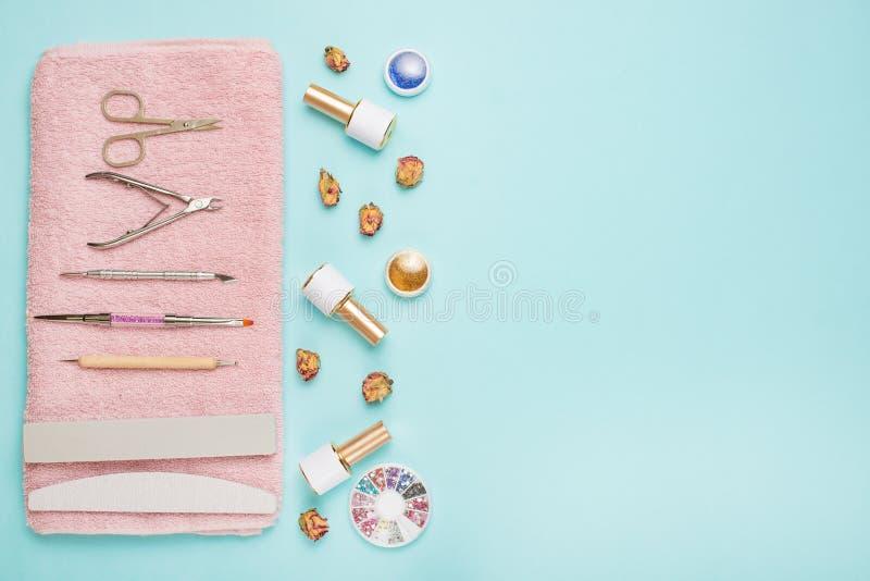 Ein Satz kosmetische Werkzeuge für Maniküre und Pediküre auf einem blauen Hintergrund Gelpolituren, Nagelfeilen und Quetschwalzen stockfoto
