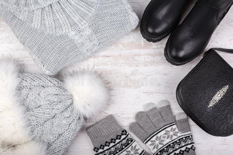 Ein Satz moderne Winterfrauen ` s Kleidung Wollstrickjacke, Schuhe, Handtasche, Pelzhut und Handschuhe auf weißem Hintergrund stockfoto