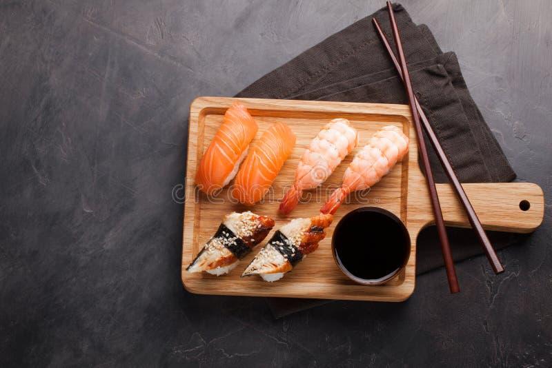 Ein Satz Sushi mit Lachsen, Garnele und Aal mit einer Schüssel Sojasoße und hölzernen Essstäbchen auf einem hölzernen Brett Köstl stockfotos