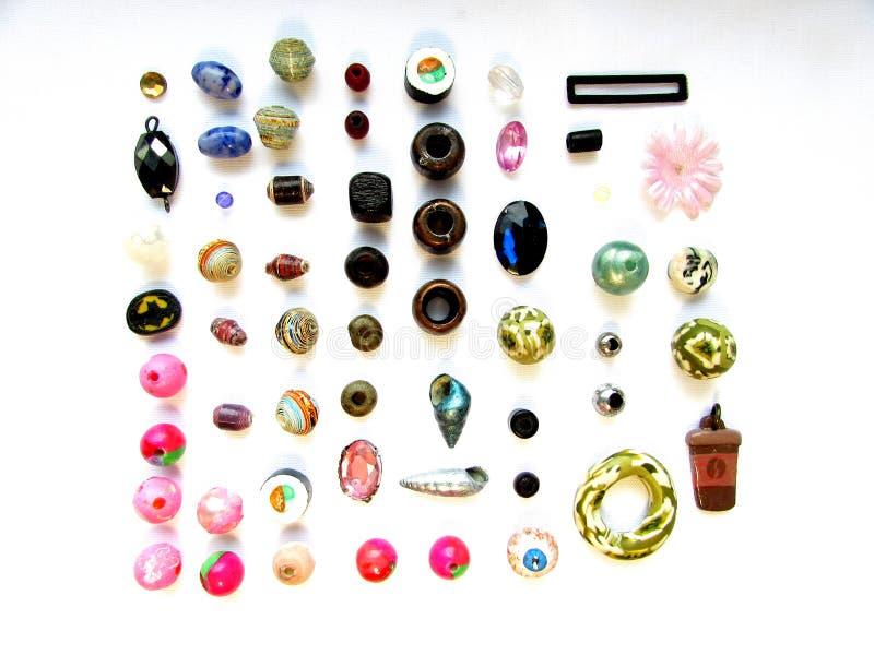 Ein Satz verschiedene Perlen, Muscheln und Zusatzeinzelteile lokalisiert auf einem weißen Hintergrund lizenzfreies stockbild
