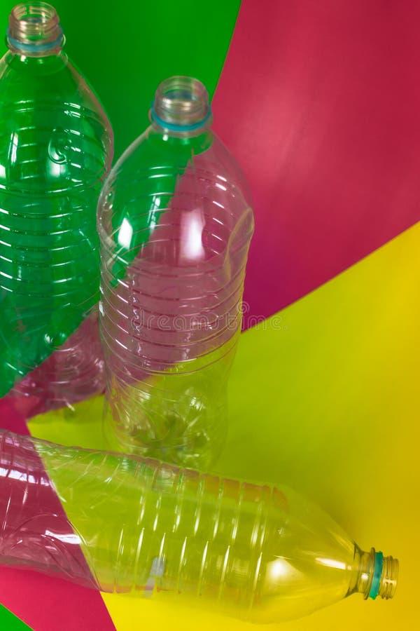 Ein Satz von 3 leer und von recyclebaren Wasserflaschen, ohne Kappen, blaue Dichtung, auf einem farbigen vibrierenden Grün, Weinr stockfotografie