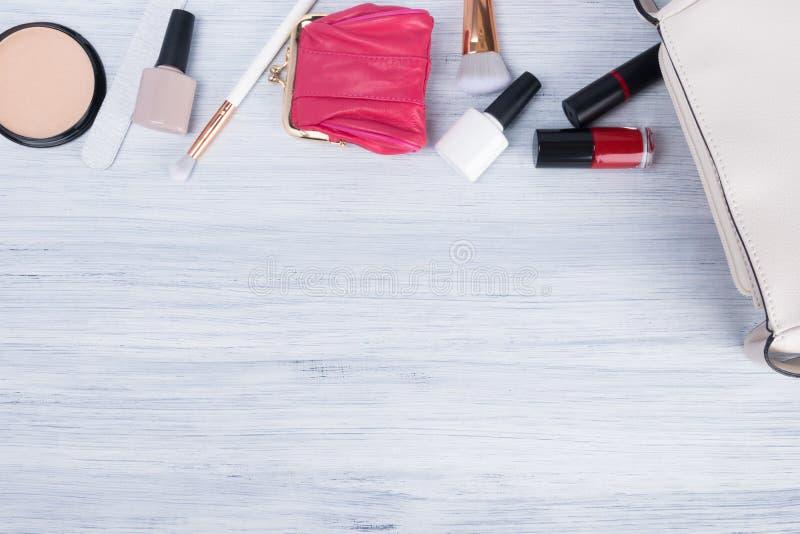 Ein Satz Zusätze, Einzelteile und Kosmetik der Frauen für das Anwenden des Makes-up, die nahe bei einer weißen Handtasche liegen, stockfotografie