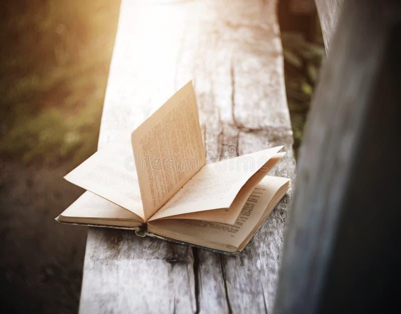 Ein schäbiges Buch liegt auf einer alten Holzbank stockfotos