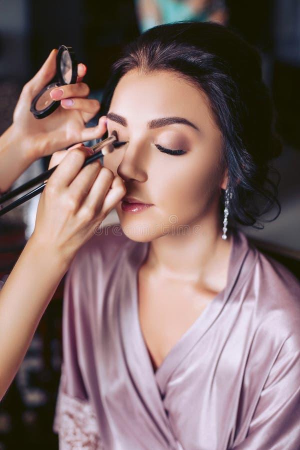 Ein schöner Brautmaskenbildner wendet Make-up an Hochzeits-Morgen der Braut lizenzfreie stockbilder