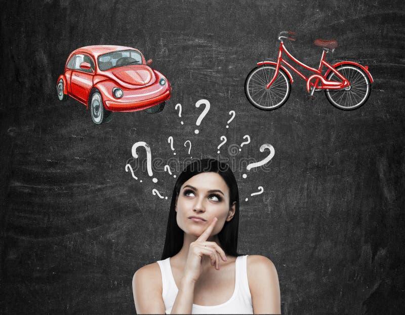 Ein schöner Brunette, den Frau versucht, wählte die passendste Weise für das Reisen oder das Austauschen Zwei Skizzen eines Autos stockfoto