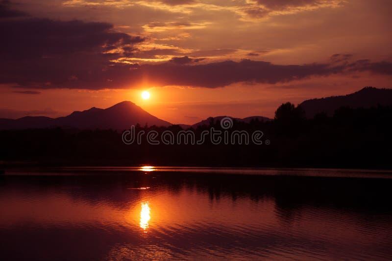 Ein schöner, bunter Sonnenuntergang über den Bergen, ein See und ein Wald in den purpurroten Tönen Abstrakte, helle Landschaft lizenzfreie stockfotografie