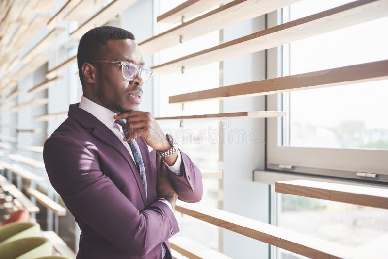 Ein schöner junger Afroamerikaner, der eine ungefähr ernste Idee denkt Überzeugt, wenn unternehmerische Entscheidungen getroffen  lizenzfreie stockfotografie