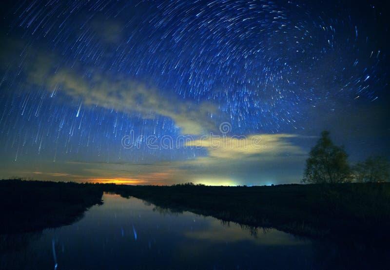 Ein schöner nächtlicher Himmel, die Milchstraße, gewundene Sternspuren und die Bäume lizenzfreie stockbilder