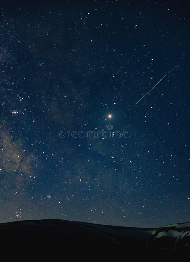 Ein schöner Schuss eines erstaunlichen Himmels voll der atemberaubenden Sterne nachts über den Hügeln stockfotos