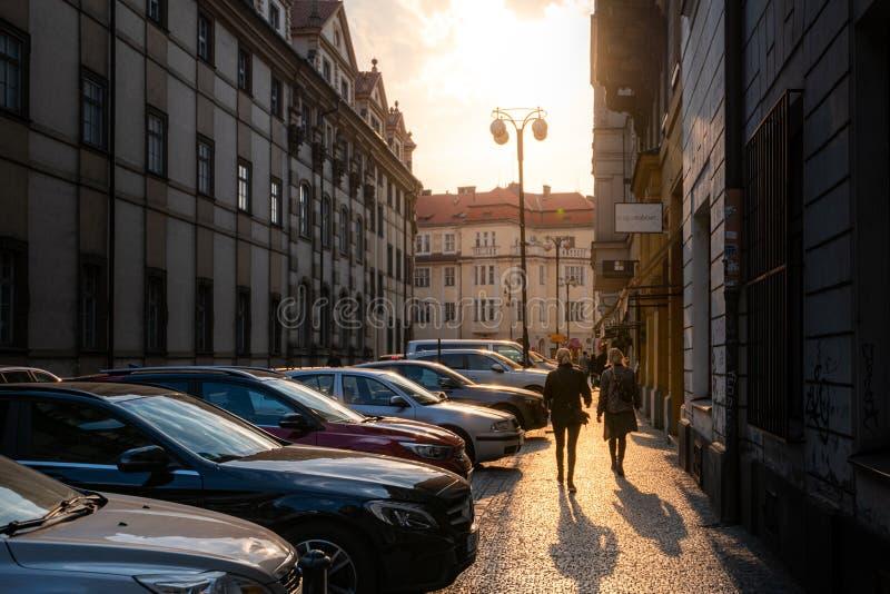 Ein schöner Schuss unten einer von traditionellen Pflasterstraßen Pragues bei Sonnenuntergang mit Touristen im Vordergrund stockfoto