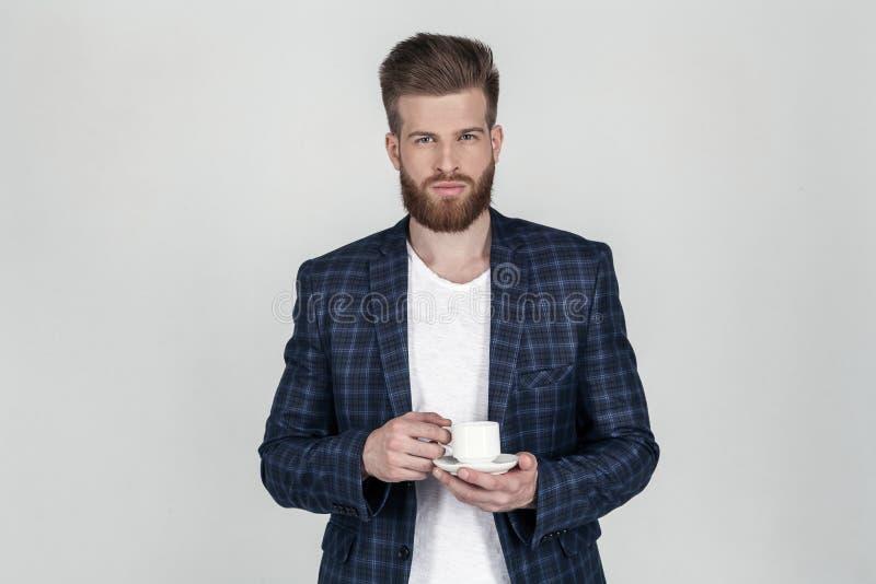Ein schöner sexy bärtiger Geschäftsmann in einer Jacke betrachtet die Kamera einen Tasse Kaffee in seinen Händen halten, steht er lizenzfreie stockfotografie