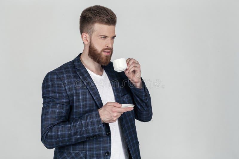 Ein schöner sexy bärtiger Geschäftsmann in einer Jacke betrachtet die weite Stellung im Profil einen Tasse Kaffee in seinen Hände lizenzfreies stockbild
