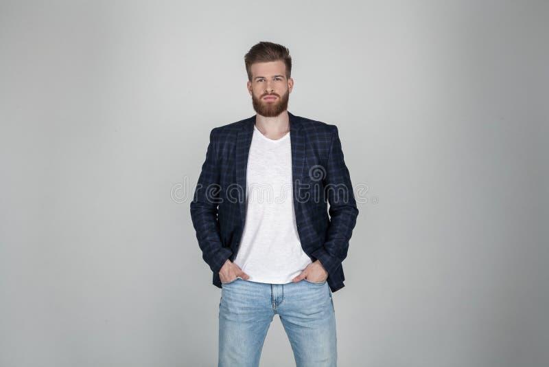 Ein schöner sexy bärtiger Mann in einer Jacke hält seine Hände auf seinen Jeans und Blicke an der Kamera er steht vor dem Wei? stockfotografie