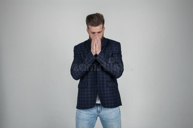 Ein schöner sexy bärtiger Mann mit einer schönen Frisur schließt ihr Gesicht mit ihren Händen ein Mann ist enttäuscht angekleidet lizenzfreie stockbilder