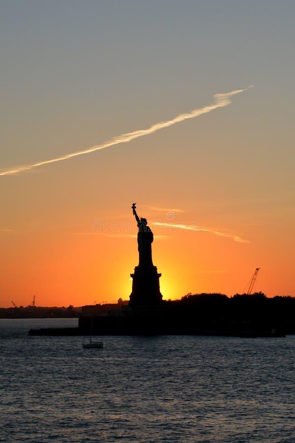 Ein schöner Sonnenuntergang mit einer Statue silhouettiert gegen den Himmel lizenzfreie stockfotografie