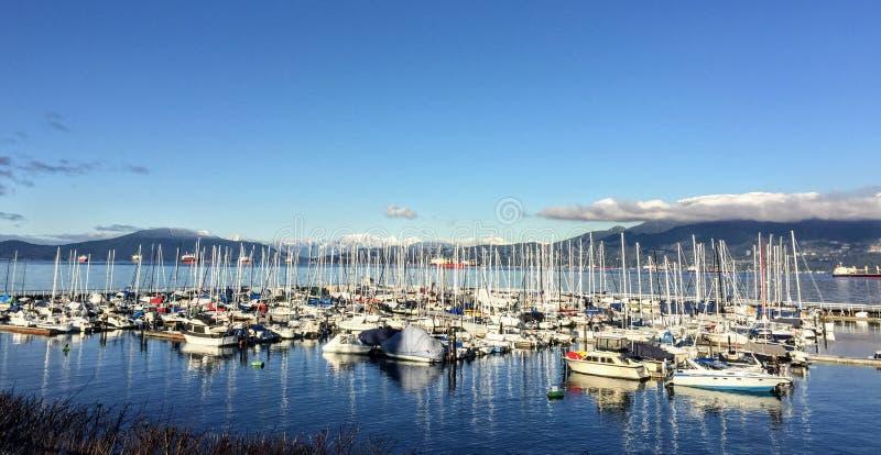 Ein schöner sonniger Wintertag einen Jachthafen übersehend verpackt mit Segelbooten entlang einem vieler Strände in Vancouver stockfotografie