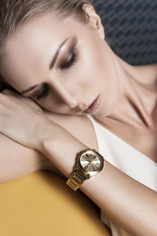 Ein schönes blondes Mädchen, das ein helles weißes Kleid und Uhren trägt, entspannt sich auf einem gelben Lederstuhl Werbung, mod stockfotografie