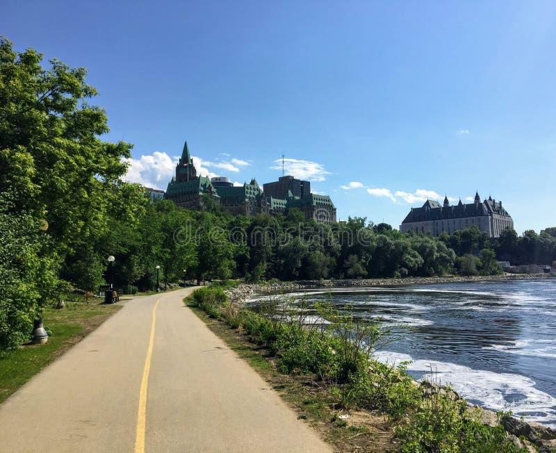 Ein schönes Fahrrad und ein Gehweg entlang dem Ottawa-Fluss an einem sonnigen Sommertag mit blauem Himmel Das Oberste Gericht von stockfotos