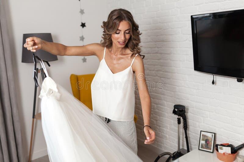 Ein schönes gelocktes Mädchen, eine zukünftige Braut, die ein Hochzeitskleid in ihrem Haus vor der Hochzeit misst lizenzfreie stockfotografie