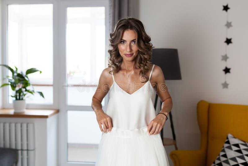 Ein schönes gelocktes Mädchen, eine zukünftige Braut, die ein Hochzeitskleid in ihrem Haus vor der Hochzeit misst stockfoto