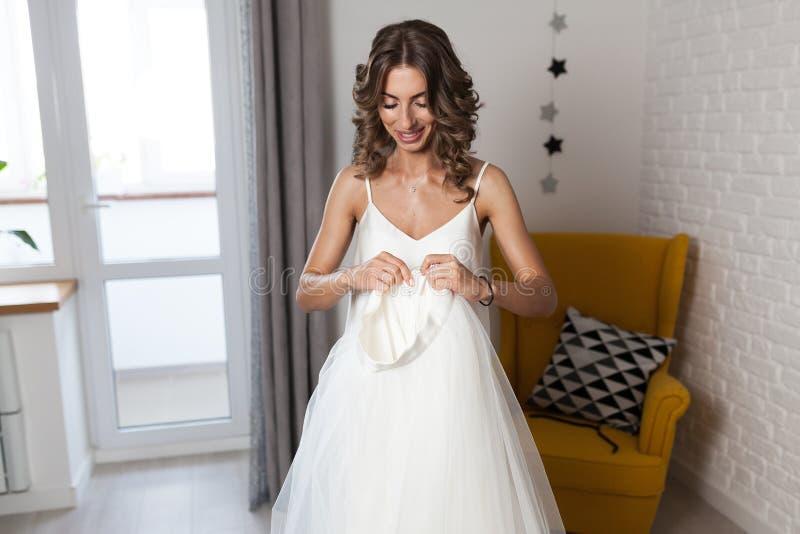 Ein schönes gelocktes Mädchen, eine zukünftige Braut, die ein Hochzeitskleid in ihrem Haus vor der Hochzeit misst stockbilder