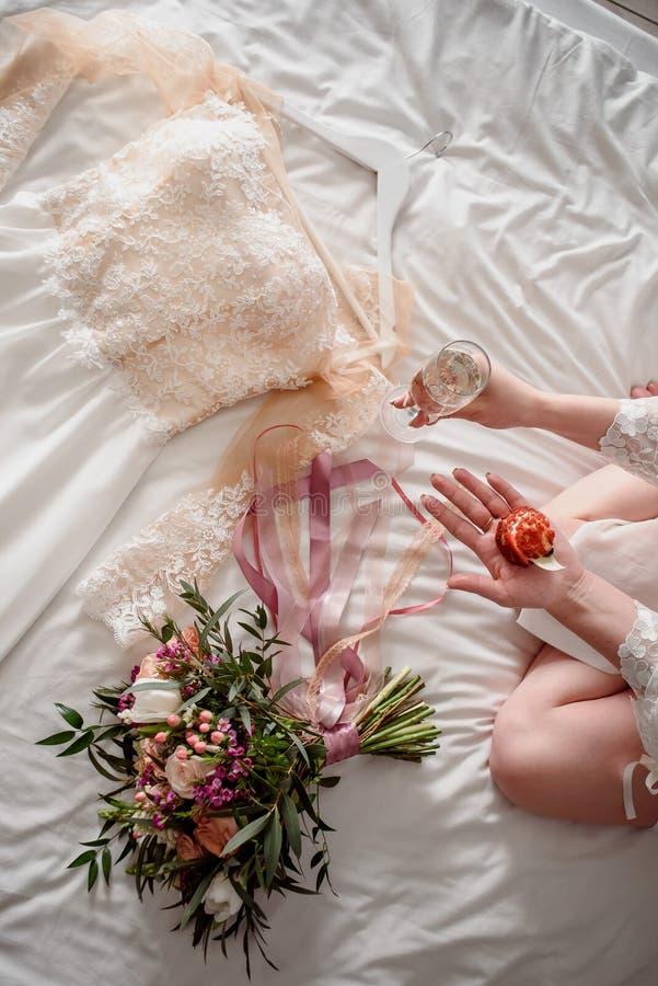 Ein schönes Hochzeitskleid liegt auf dem Bett nahe bei dem Braut ` s Blumenstrauß lizenzfreie stockbilder