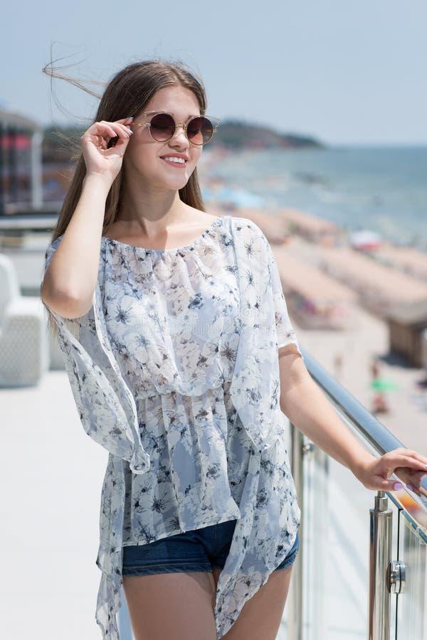 Ein schönes junges Mädchen in der Sommerkleidung und in den Sonnenbrillen auf einem Luxushotelhintergrund Die vorbildliche Frau i stockfotografie