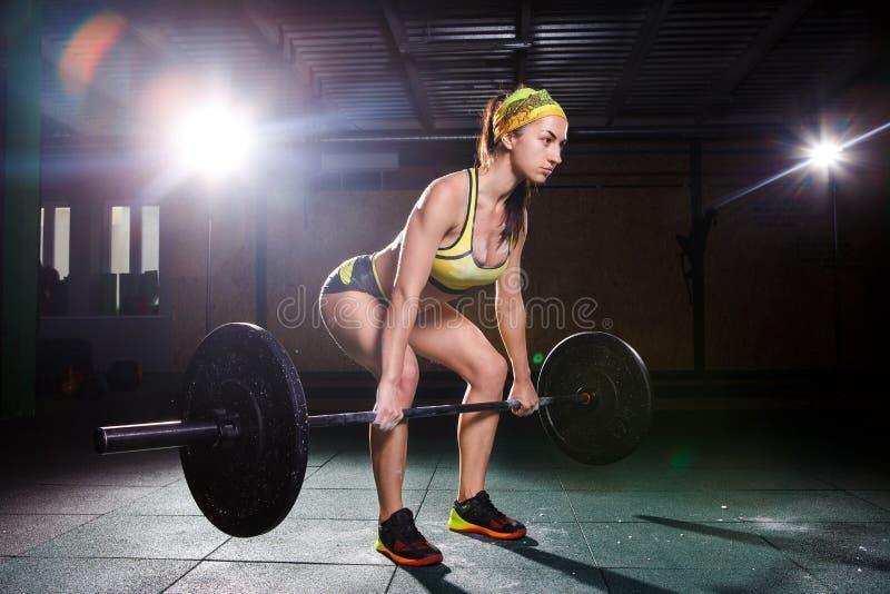 Ein schönes junges Mädchen in der Turnhalle bildet die Muskeln der Beine aus und Rückseite, deaet Übungen deadlift, sitzt mit Gew stockbilder