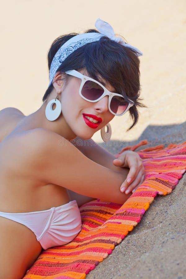 Ein schönes junges Mädchen im Retro Blick mit den roten Lippen in einem weißen Schalter stockbild