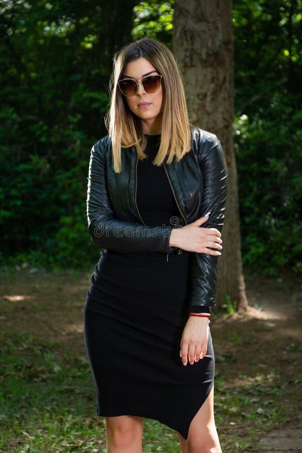 Ein schönes junges Mädchen im schwarzen Kleid und Lederjacke und Sonnenbrille, die in der Natur an einem sonnigen Frühlingstag au stockfotos