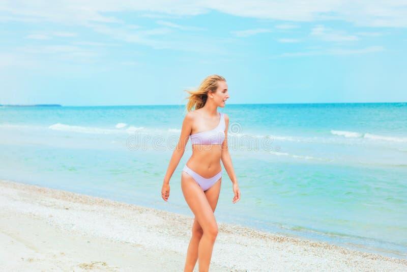 Ein schönes junges Mädchen mit dem blonden Haar im rosa Badeanzug, der auf Strand im Meer läuft stockfoto