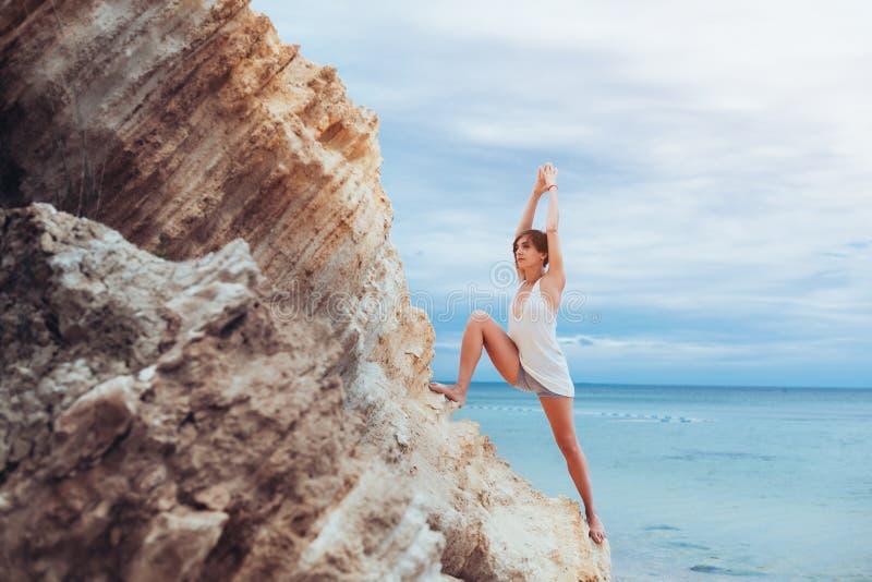 Ein schönes junges Mädchen mit dem kurzen Haar wird kurz gesagt und ein übendes Yoga des weißen Trikots gekleidet stockfotos