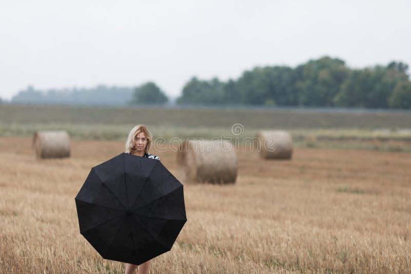 Ein schönes junges Mädchen mit einem Regenschirm steht auf einem Gebiet nahe einem Heuschober stockfotografie