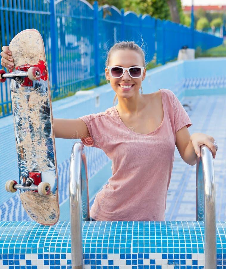 Ein schönes junges Mädchen mit einem scateboard auf der Poolleiter stockbild