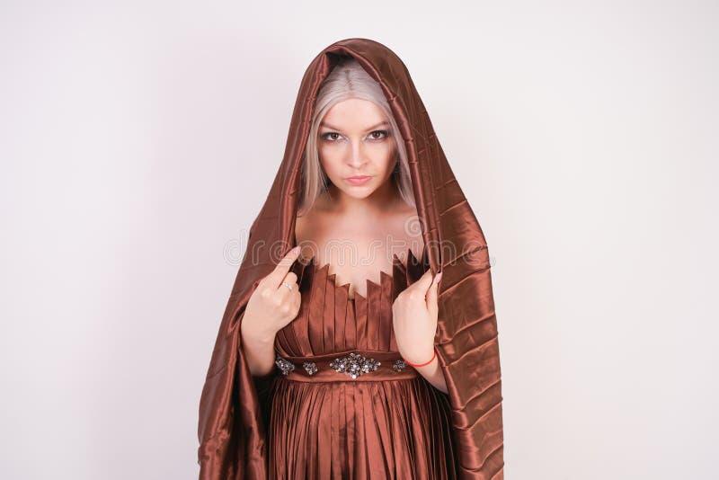 Ein schönes junges Mädchen steht in einem luxuriöses gefalteten Kleid des Abends Braun mit einer Stoffabdeckung ihr Haar und Kopf stockbilder