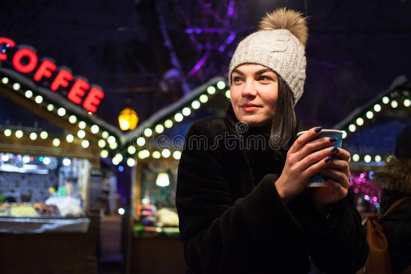 Ein schönes junges Mädchen trinkt heißen Kaffee am Weihnachtsmarkt Konzept-Lebensstil, städtisch, Winter, Ferien stockfoto