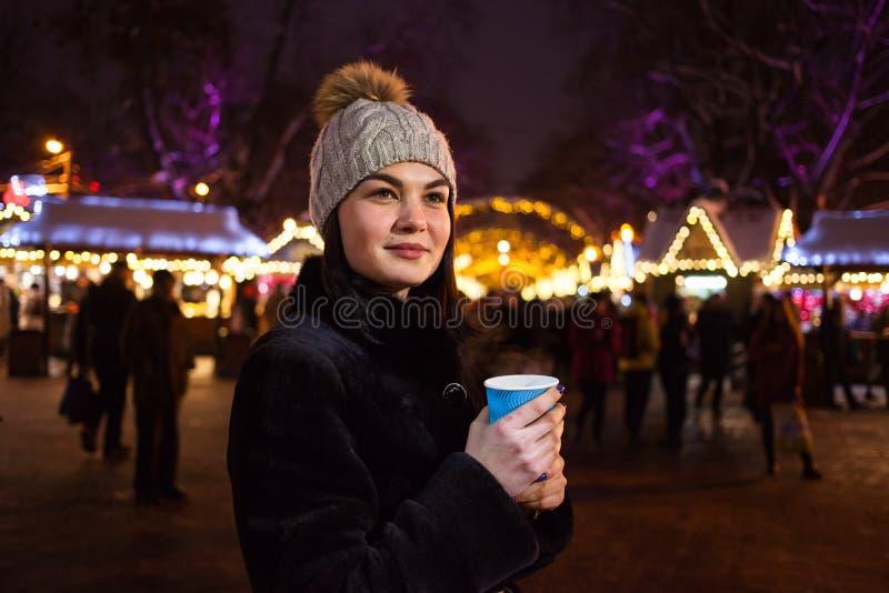 Ein schönes junges Mädchen trinkt heißen Kaffee am Weihnachtsmarkt Konzept-Lebensstil, städtisch, Winter, Ferien stockbild