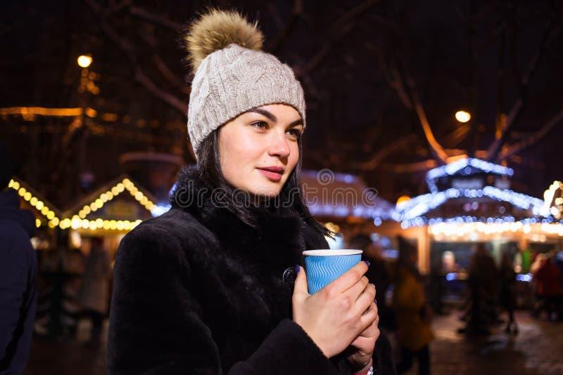 Ein schönes junges Mädchen trinkt heißen Kaffee am Weihnachtsmarkt Konzept-Lebensstil, städtisch, Winter, Ferien lizenzfreie stockbilder